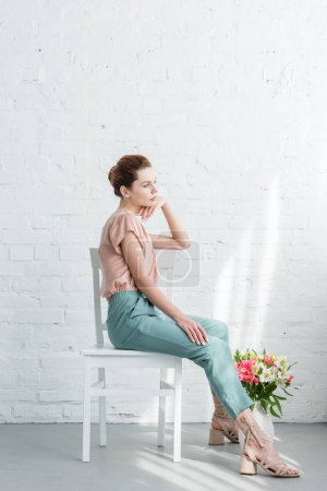 thoughtful young woman sitting on chair with flowers on floor in front of white brick wall