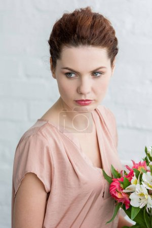 Photo pour Gentil jeune femme avec de belles fleurs devant le mur de briques blanches - image libre de droit