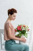side view of attractive young woman holding vase with flowers while sitting on chair in front of white brick wall