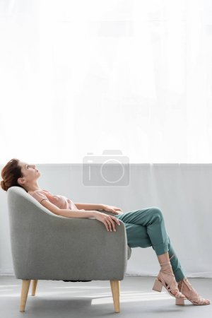 attractive young woman relaxing on comfy armchair at home