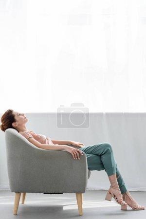 Photo pour Jolie jeune femme détente sur fauteuil confortable à la maison - image libre de droit