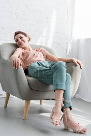 happy young woman relaxing on armchair at home