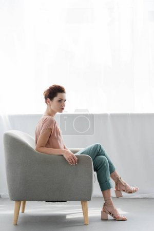 side view of beautiful young woman sitting on armchair at home