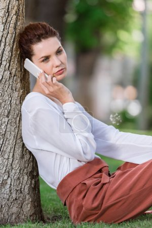 beautiful young woman talking by phone while leaning back on tree trunk in park