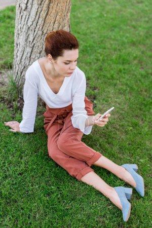 Photo pour Belle jeune femme en utilisant smartphone tout en étant assis sur l'herbe dans le parc - image libre de droit