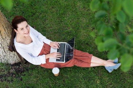 Photo pour Vue de dessus de belle jeune femme travaillant avec ordinateur portable tout en étant assis sur l'herbe avec papier café - image libre de droit