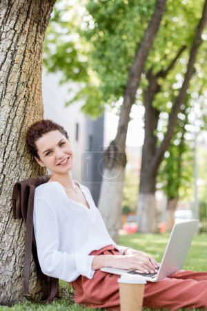 happy young freelancer working with laptop while leaning back on tree trunk in park and looking at camera