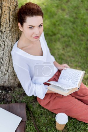 high angle view of happy young woman with book leaning back on tree trunk in park and looking at camera