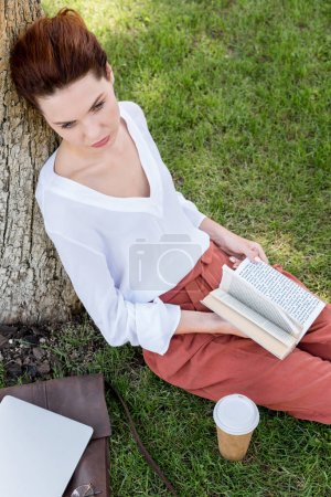 high angle view of beautiful young woman with book leaning back on tree trunk in park