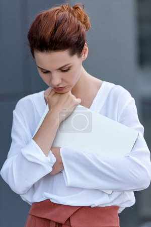 Photo for Close-up portrait of young woman holding laptop - Royalty Free Image