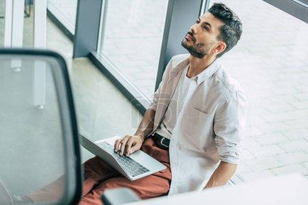 Foto de Vista de ángulo alto del hombre de negocios reflexivo en ropa casual sentado en el suelo con el ordenador portátil y mirando hacia arriba - Imagen libre de derechos