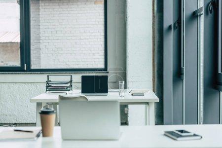 Photo pour Des bureaux avec des ordinateurs portables, du café à emporter et du verre d'eau, des cahiers et un plateau à documents - image libre de droit