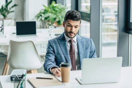 Photo pour Un homme d'affaires réfléchi assis sur son lieu de travail près d'un ordinateur portable et d'un café pour aller - image libre de droit