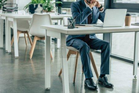 Photo pour Vue recadrée de l'homme d'affaires en costume assis sur le lieu de travail au bureau - image libre de droit