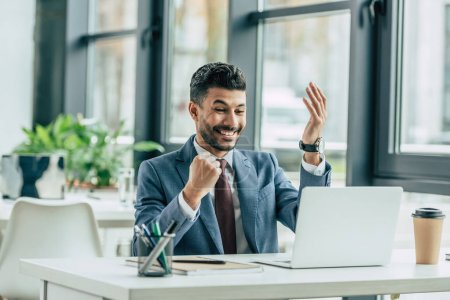 excited businessman showing winner gesture while sitting at workplace near laptop