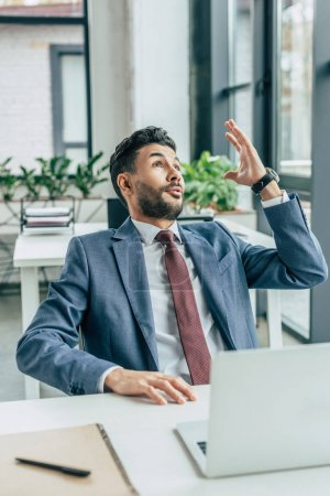 Photo for Excited businessman showing idea gesture while sitting at workplace and looking up - Royalty Free Image