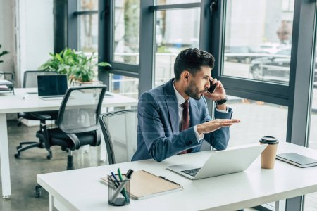 concentrated businessman gesturing while sitting at workplace and talking on smartphone