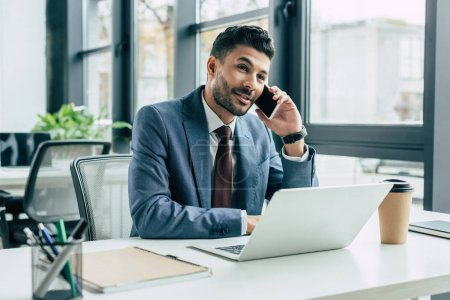 smiling businessman talking on smartphone while sitting at workplace near laptop