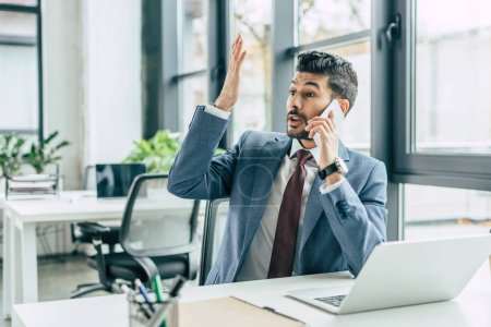 Photo for Discouraged businessman showing indignation gesture while sitting at workplace and talking on smartphone - Royalty Free Image