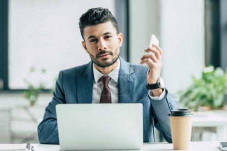Photo pour Ennuyé homme d'affaires regardant la caméra tout en étant assis près de l'ordinateur portable et tenant smartphone - image libre de droit