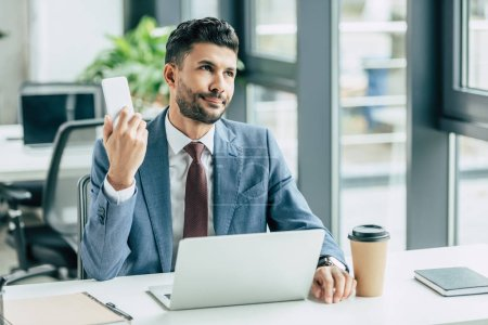 Photo for Bored businessman looking away while sitting near laptop and holding smartphone - Royalty Free Image