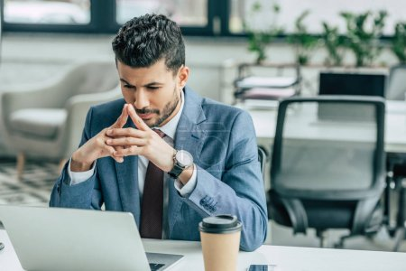 Photo for Thoughtful businessman looking at laptop while sitting at workplace - Royalty Free Image
