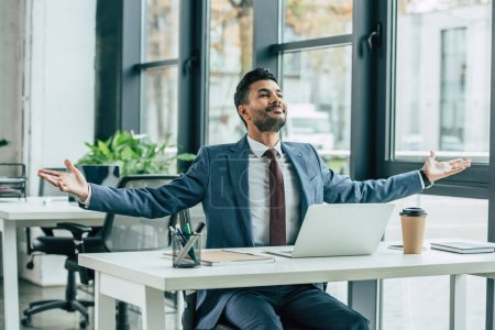 Photo for Happy businessman showing wow gesture while sitting at workplace - Royalty Free Image