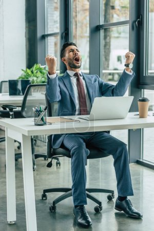 Photo for Happy businessman screaming and showing winner gesture while sitting at workplace - Royalty Free Image