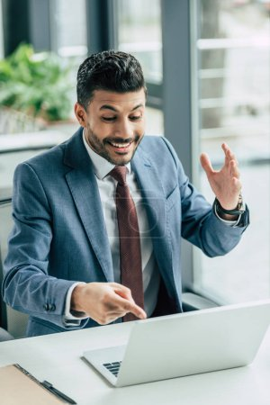 surprised businessman showing with finger at laptop while sitting at workplace