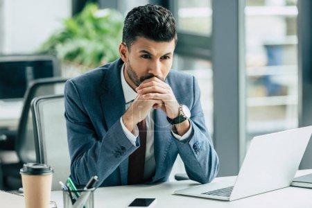 Photo pour Cher homme d'affaires assis sur le lieu de travail près d'un ordinateur portable et regardant loin - image libre de droit