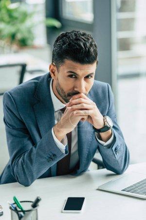 Photo pour Homme d'affaires réfléchi regardant la caméra tout en étant assis sur le lieu de travail - image libre de droit