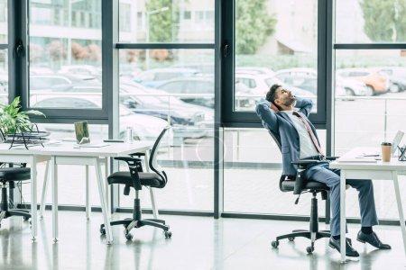 Photo pour Jeune homme d'affaires assis sur son lieu de travail dans un bureau moderne et spacieux - image libre de droit