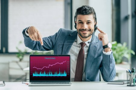 cheerful call center operator pointing with finger at laptop with trading infographics on screen