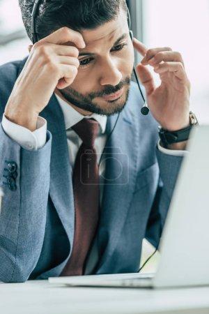 Photo pour Ennuyé opérateur de centre d'appels dans un casque d'écoute regardant un ordinateur portable assis au travail - image libre de droit