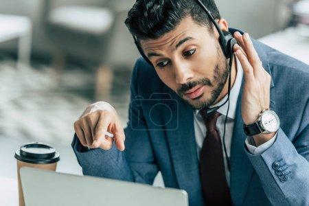 Foto de Operador de centros de llamadas concentrados en audífonos que apuntan con el dedo al ordenador portátil. - Imagen libre de derechos