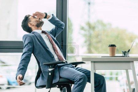 Photo pour Un homme d'affaires épuisé assis sur son lieu de travail et souffrant de maux de tête - image libre de droit