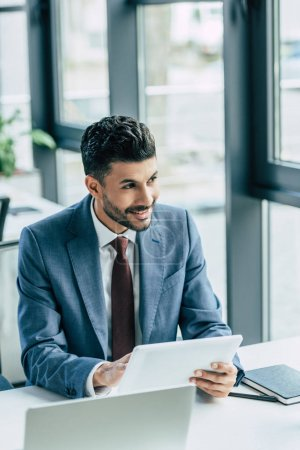 Photo pour Homme d'affaires souriant regardant loin tout en tenant tablette numérique - image libre de droit