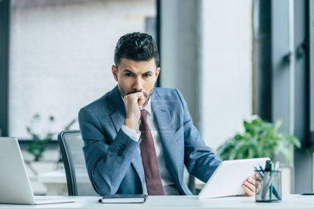 thoughtful businessman holding laptop and looking at camera while sitting at workplace