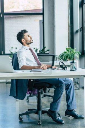 opérateur de centre d'appels réfléchi regardant loin tout en étant assis sur le lieu de travail près de l'ordinateur portable et casque
