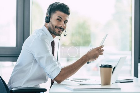 cheerful call center operator holding digital tablet and looking at camera