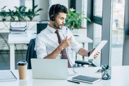 Foto de Operador de centros de llamadas concentrados que utiliza tableta digital mientras se sienta en el lugar de trabajo cerca de portátil y café para ir. - Imagen libre de derechos