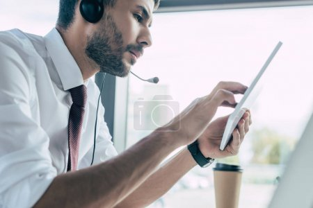 Photo for Selective focus of serious call center operator using digital tablet - Royalty Free Image