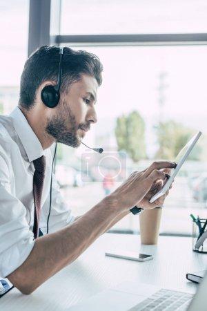 Foto de Operador de centros de llamadas serios usando tableta digital mientras está sentado en el lugar de trabajo. - Imagen libre de derechos