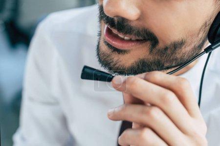 """Photo pour Vue partielle d'un opérateur de centre d'appels souriant en utilisant un casque d """"écoute - image libre de droit"""