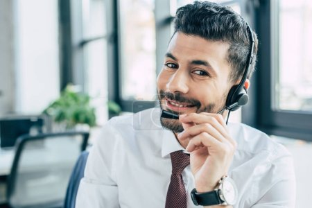 handsome call center operator smiling at camera while using headset