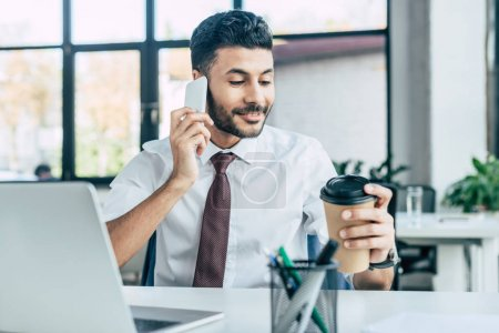Photo for Smiling businessman holding coffee to go while talking on smartphone - Royalty Free Image