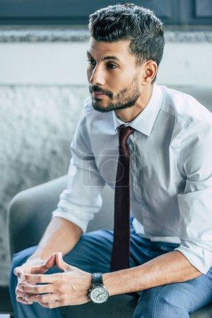 Photo pour Homme d'affaires réfléchi assis dans un fauteuil avec les mains pliées - image libre de droit