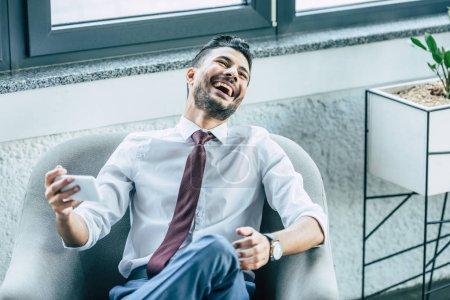 Photo pour Un homme d'affaires gai assis en fauteuil et riant pendant une discussion vidéo sur un téléphone intelligent - image libre de droit