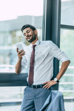 handsome businessman smiling and holding hand on hip during video chat on smartphone