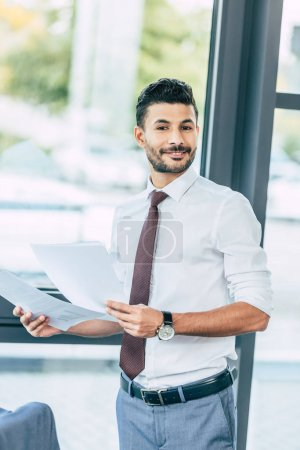 Photo for Handsome businessman holding documents, smiling and looking at camera - Royalty Free Image